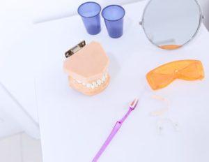 teeth-denture-safety-glasses-toothbrush-mirror-and-teeth-aligner-on-table_23-2147879121